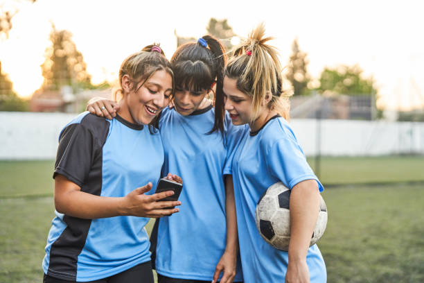 Soccer players showing mobile phone to friends stock photo