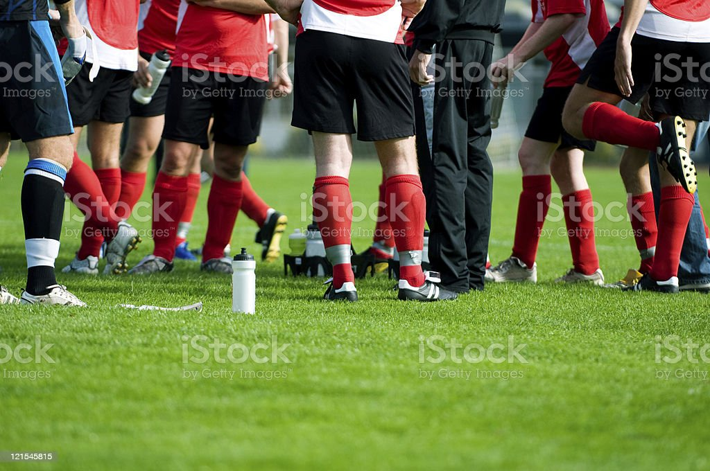Soccer players stand together at halftime during football match stock photo