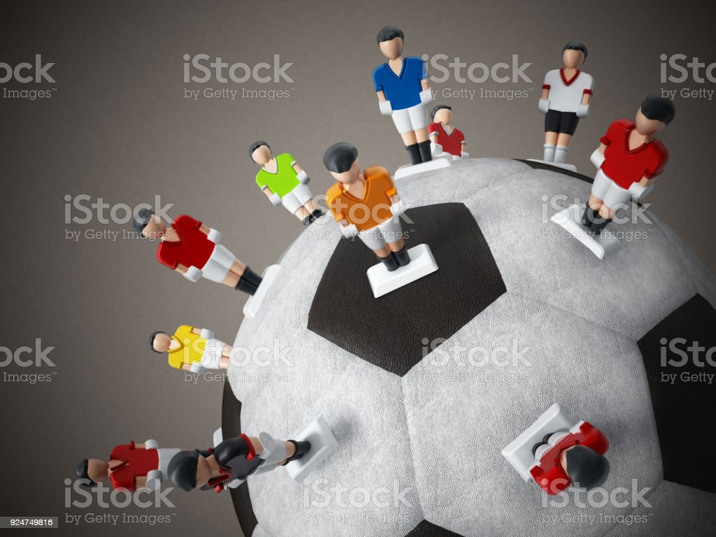 Soccer players standing around black and white soccer ball stock photo