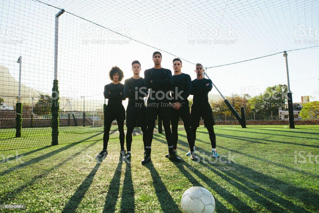 Joueurs de foot debout ensemble sur terrain photo libre de droits