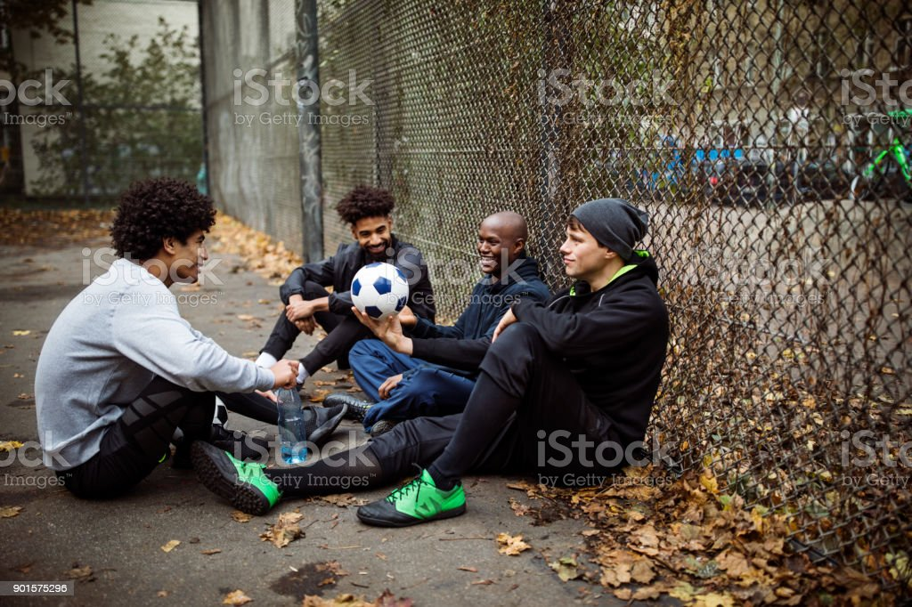 Soccer players talking while sitting against fence stock photo
