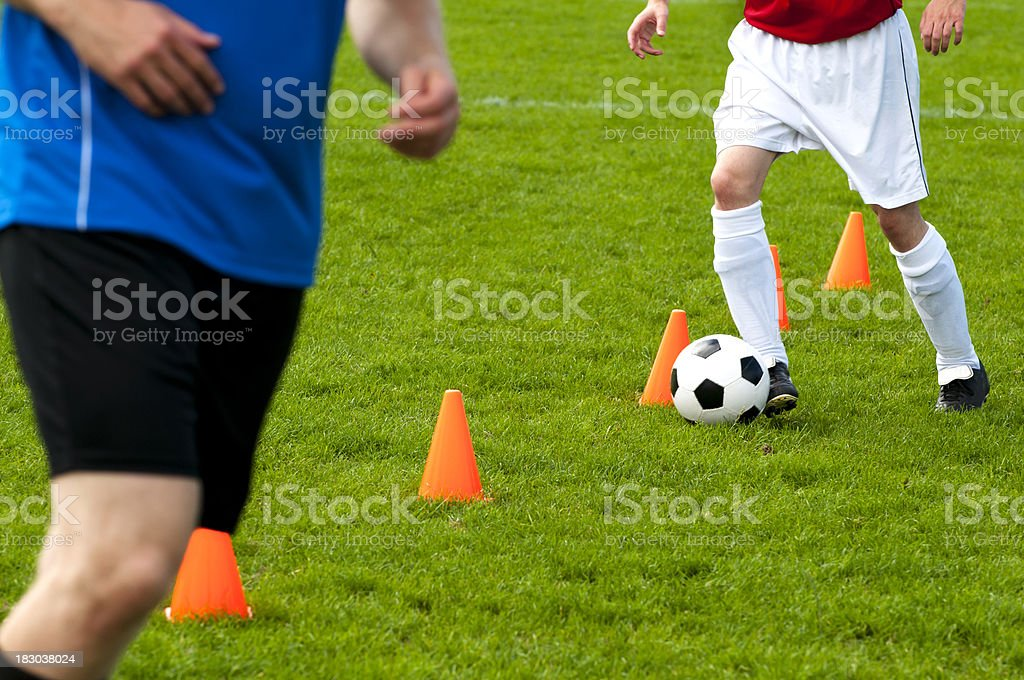 Soccer players warm up and run past cones with ball royalty-free stock photo