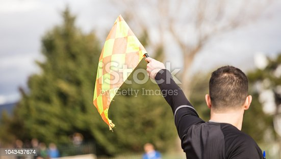 istock Soccer referee assistant raises the flag with his hand. Blur blue sky, nature, players background, close up view, details. 1043437674