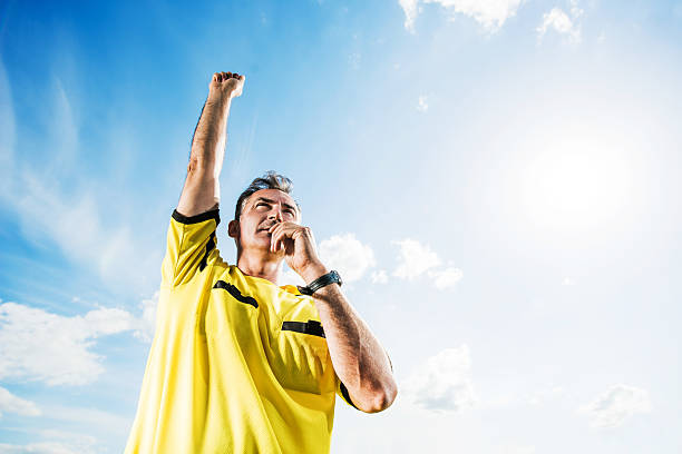 Soccer referee blowing his whistle against the sky. Low angle view of referee raising his arm and blowing his whistle against the sky. referee stock pictures, royalty-free photos & images