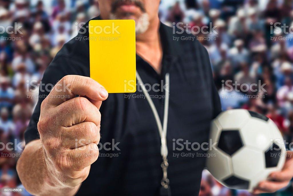 Árbitro de futebol segurando um cartão amarelo na câmera - foto de acervo