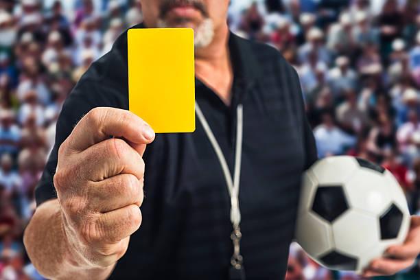 Arbitre de football en tenant un carton jaune à la caméra - Photo
