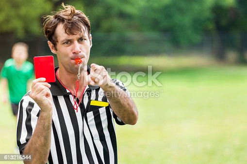 Serious mid adult Caucasian male referee looks at the camera and points while holding up a red card. he is also blowing a whistle. A young soccer player wearing a green jersey is in the background. Copy space is available.