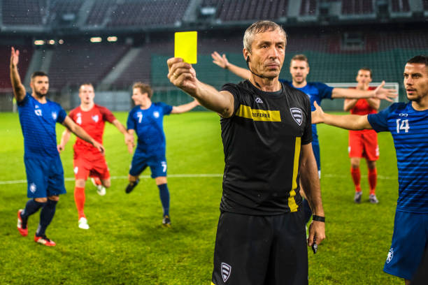 Soccer referee showing yellow card Soccer referee surrounded by players of both teams while he is holding a yellow card. referee stock pictures, royalty-free photos & images