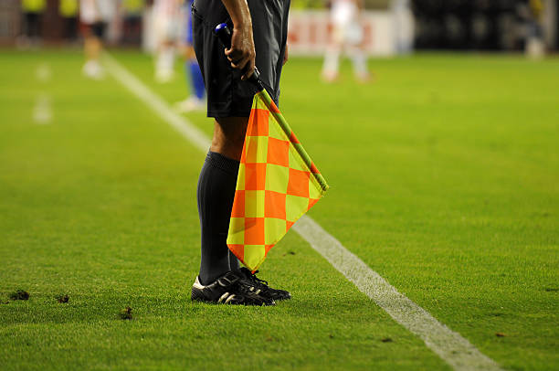 Soccer referee's checkered flag on a soccer field Soccer Referee holding flag referee stock pictures, royalty-free photos & images