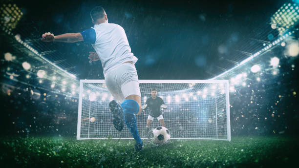 Soccer scene at night match with player in a white and blue uniform kicking the penalty kick - foto stock
