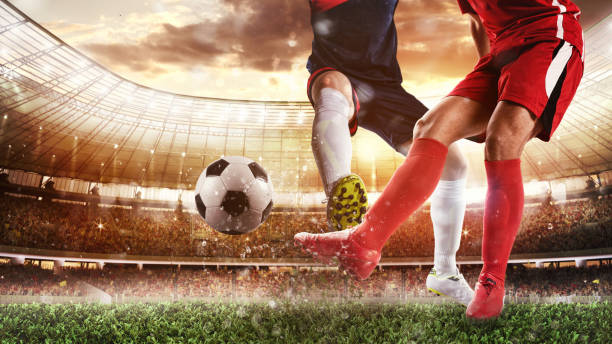 Soccer scene at the stadium with player in a red uniform kicking the ball and opponent in tackle to defend stock photo