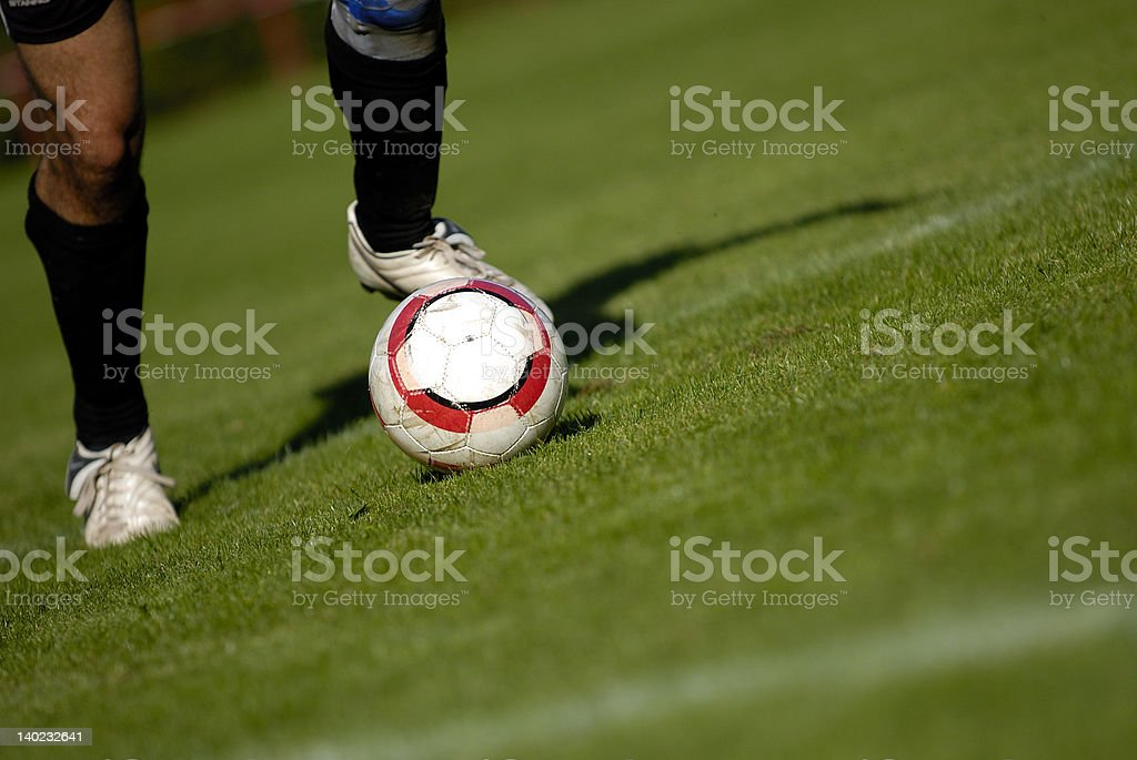 Soccer scene with two legs and ball in focus royalty-free stock photo