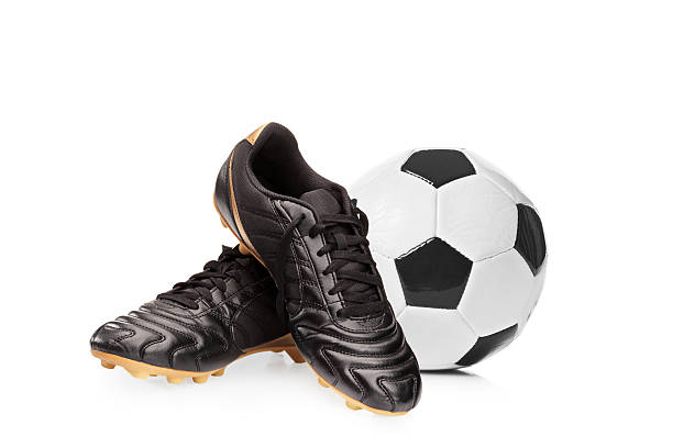 Soccer shoes and a football Football shoes and a football isolated on white background studded stock pictures, royalty-free photos & images