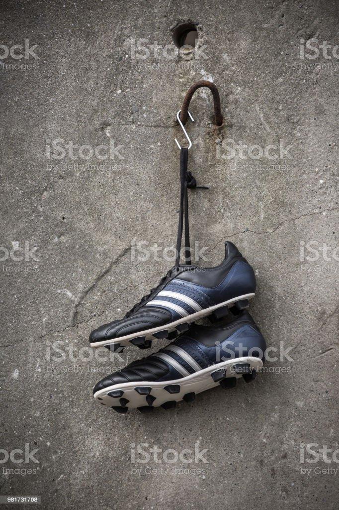 Zapatos De Fútbol Colgadas En Una Pared Concreta Foto de