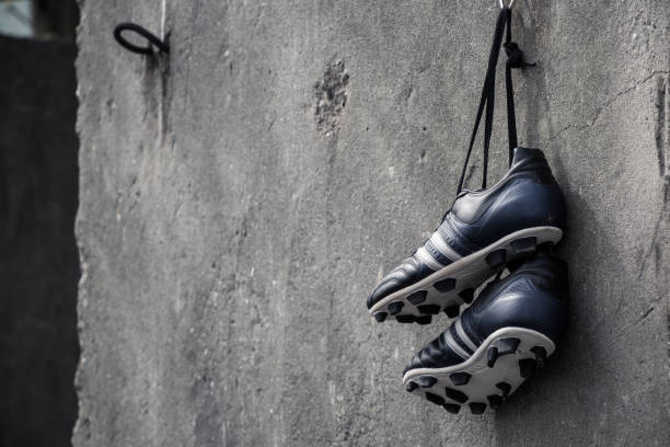 Soccer shoes hanging on a rough concrete wall. Soccer shoes hanging. studded stock pictures, royalty-free photos & images
