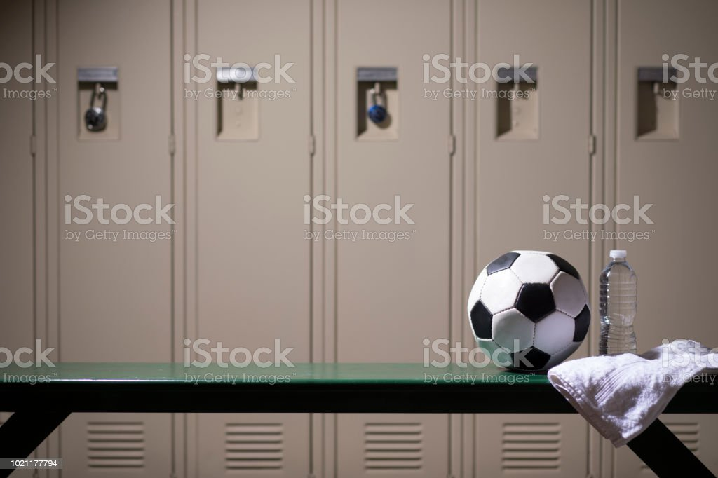 Soccer sports equipment in school gymnasium locker room. stock photo