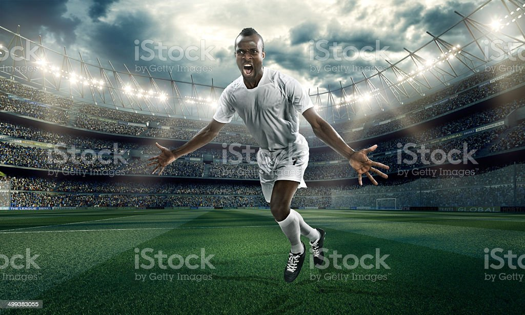 Soccer stadium and soccer player happy scoring a goal stock photo