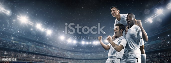 Wide angle soccer stadium with snow and rain and soccer players happy after victory. The players wear unbranded soccer uniform
