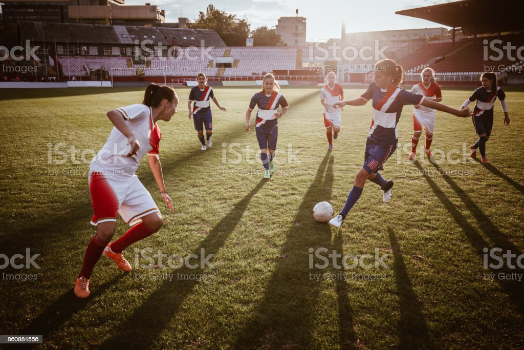 Soccer striker kicking the ball during a match on a stadium. stock photo