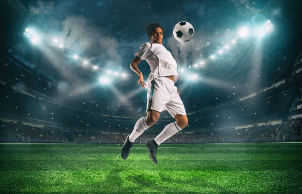 Soccer striker stops the ball with an acrobatic jump at the stadium during a night match stock photo