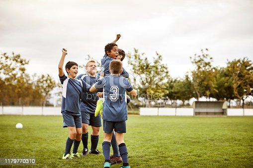 Cheerful soccer team celebrating success after match. Multi-ethnic boys are enjoying on field. They are in blue sports uniforms.