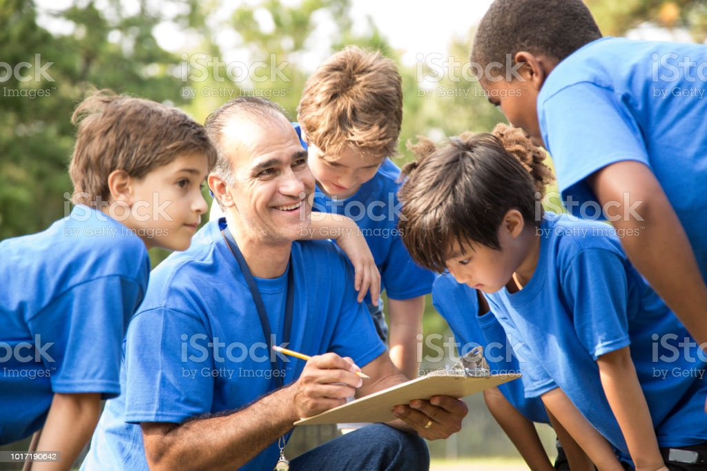 Soccer team coach explains next play to his children's team. royalty-free stock photo