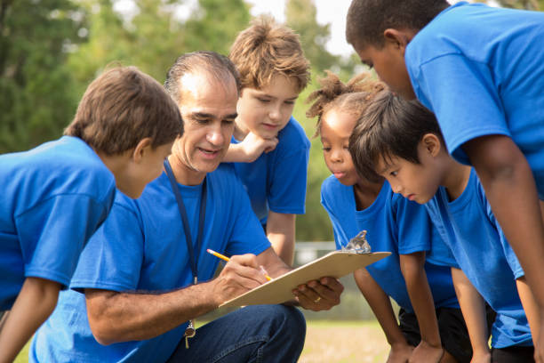Soccer team coach explains next play to his children's team. stock photo