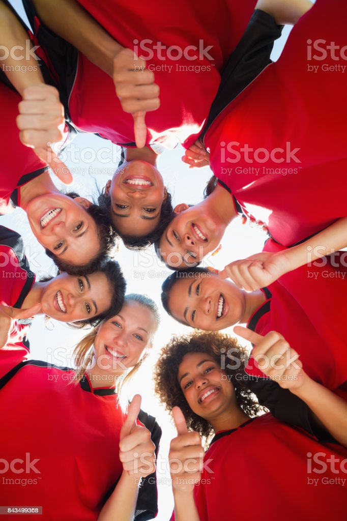 Soccer team gesturing thumbs up while forming huddle stock photo