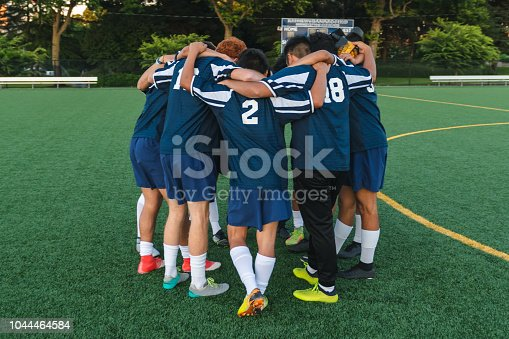 A men's soccer team huddles up with their arms around one another before their evening game on a turf field.