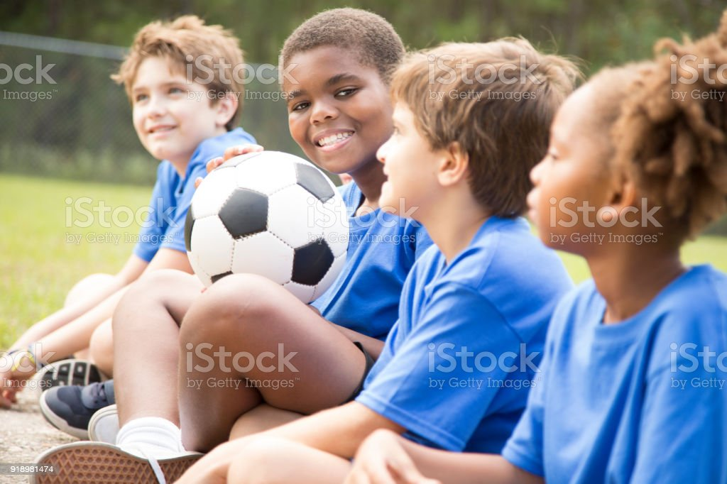 Multi-ethnic and mixed age group of school children listen to their...