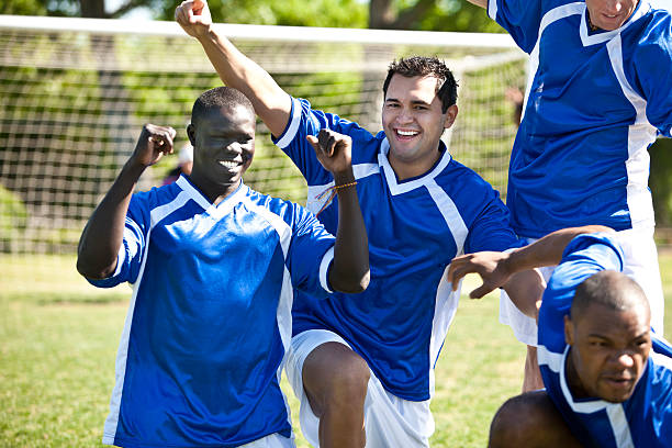 soccer team pumping fists after scoring a goal - soccer competition stock photos and pictures