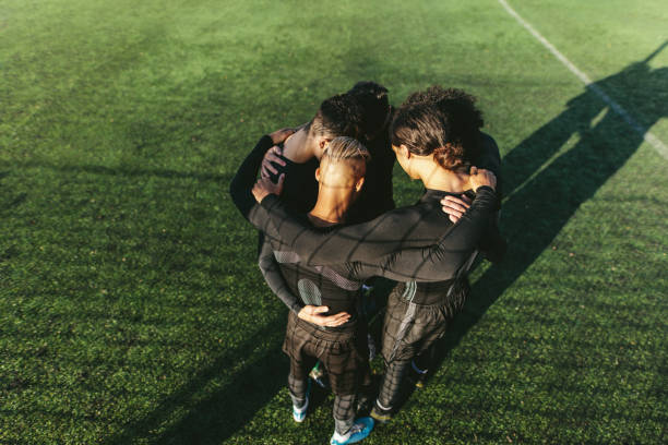 Soccer team standing in a huddle stock photo