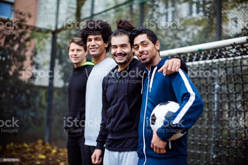 Soccer team with ball standing against goal post stock photo