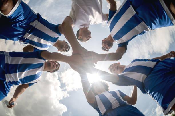 équipe de soccer avec les mains ensemble sur le terrain - équipe sportive photos et images de collection