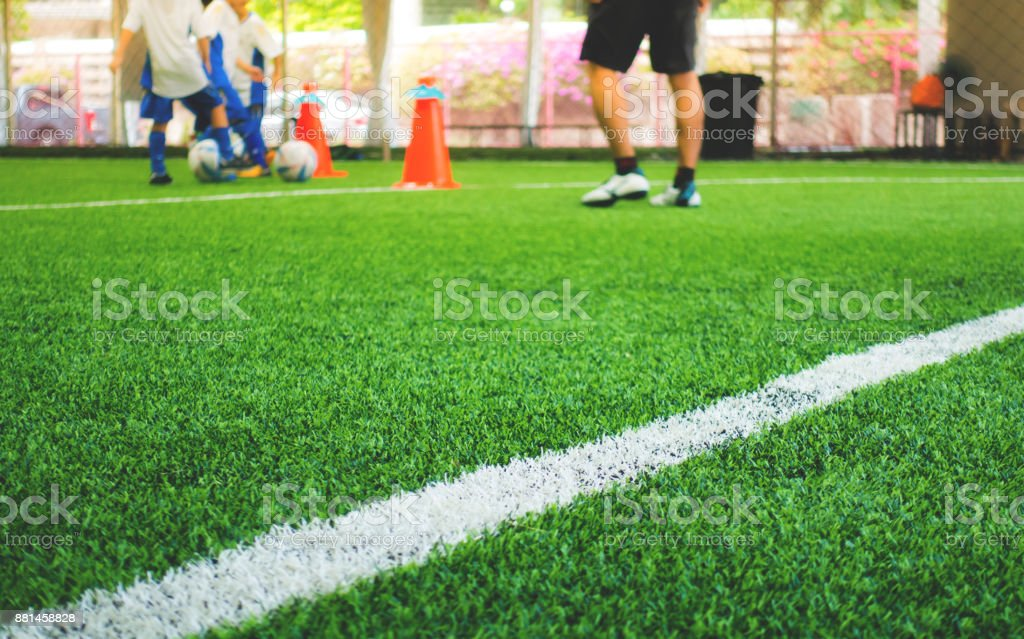 Soccer training field white line with kid training in background stock photo