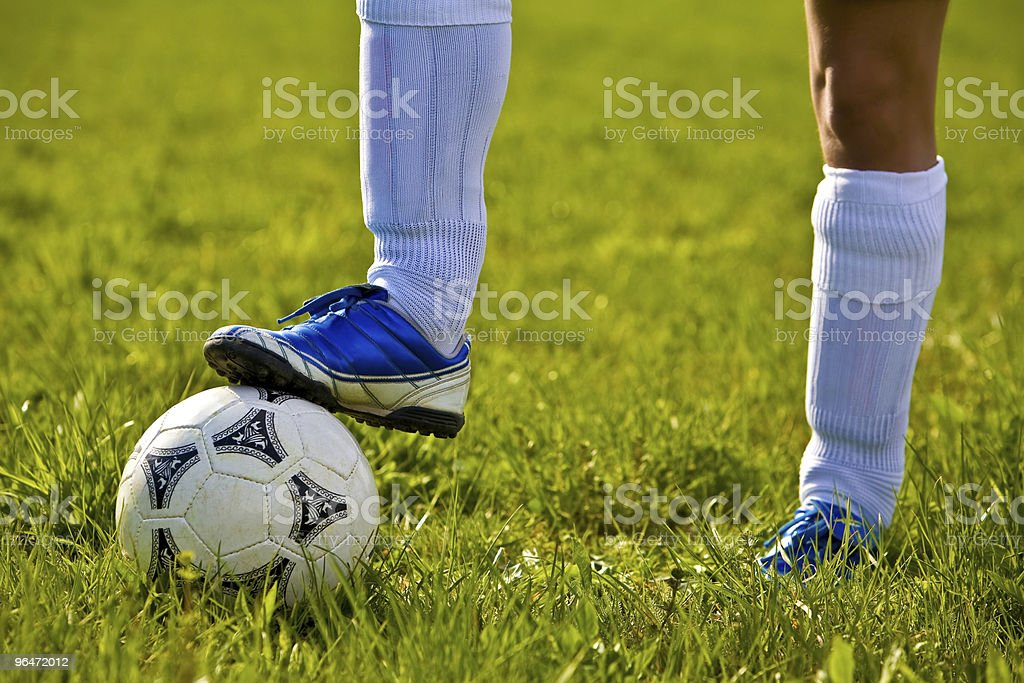 Soccerball and feet of soccer player royalty-free stock photo