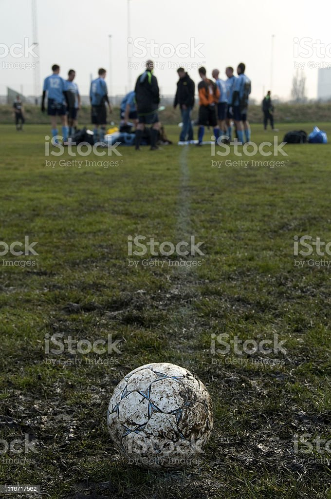 Soccerball on a muddy football field royalty-free stock photo
