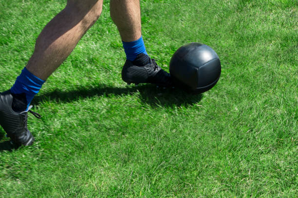 soccor player kicking abll of a green grassy field with black kelletts and balck ball stock photo