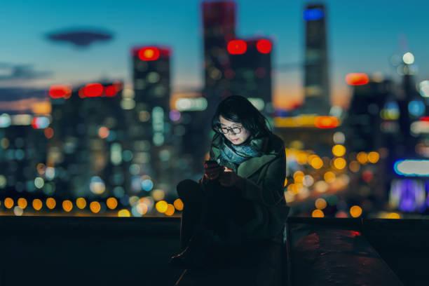 城市城市夜間的社會連接 - 僅一名中年女子 個照片及圖片檔