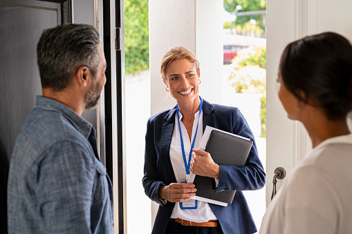 Smiling mature social counselor meeting mature couple at home. Happy multiethnic man and latin woman greeting agent at home standing near door. Successful social worker consultant on the doorstep meeting ethnic couple.