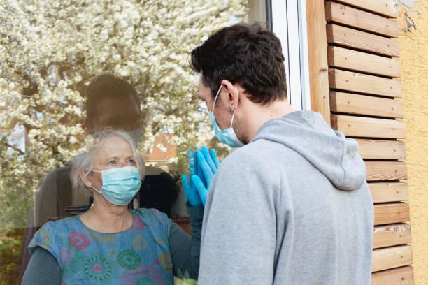 Soziale Entschärbung in Zeiten von COVID-19: Seniorin und reifer Mann schauen sich durchs Fenster an – Foto