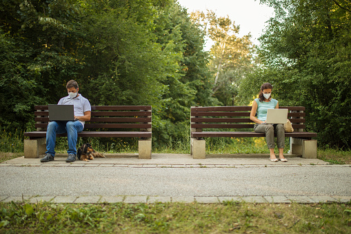 A woman and a man maintain a social distance by sitting on separate benches while using laptop at a safe distance and wearing protective face masks.