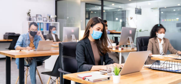 Social distance office with business team wear face mask as new normal life stock photo