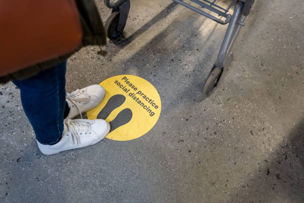 Social Distance Sign on the floor during COVID-19 stock photo