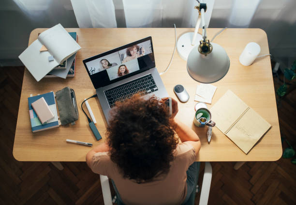 Social Distancing and Self Care: Happy Woman Teleconferencing from Home Flattening the curve: a happy woman sitting at home and talking to her friends or colleagues in a meeting using her laptop computer. adult stock pictures, royalty-free photos & images