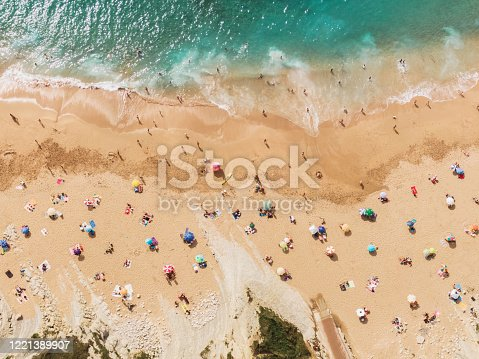 A beach in summer with a large amount of people, but who maintain social distancing measures beacuse of the Coronavirus COVID-19 outbreak. The image has been digitally modified to show a distance between people, towels, umbrellas, longer than 1.5 meters (5 feet).