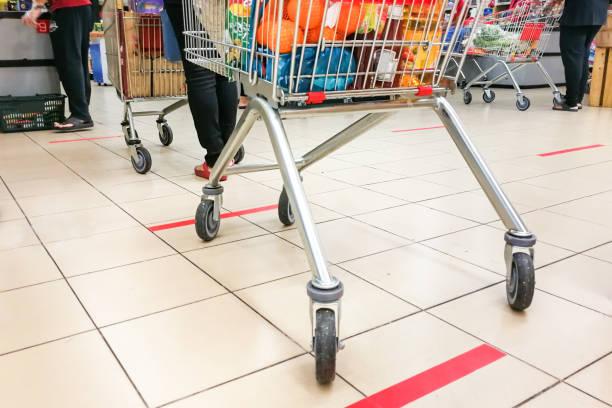 Soziale Abstand wird am Supermarkt-Zahlungsschalter praktiziert, mit 1 Meter Abstand zwischen den Menschen in der Warteschlange. – Foto