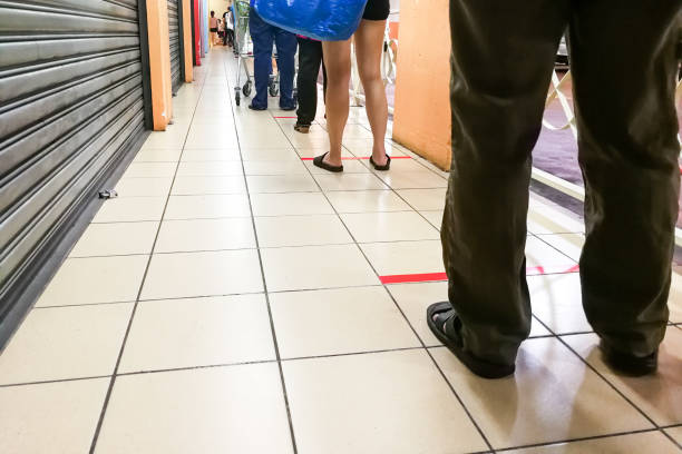 Social distancing being practiced where people are separated by a gap of at least 1 meter in queue into supermarket. stock photo