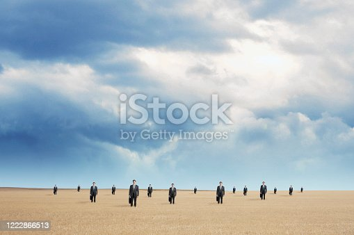 A single businessman is multiplied several times as he stands in an open field in a concept that illustrates social distancing.
