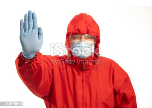 Person with mask and hand raised in red protective suit, stop concept for social distancing